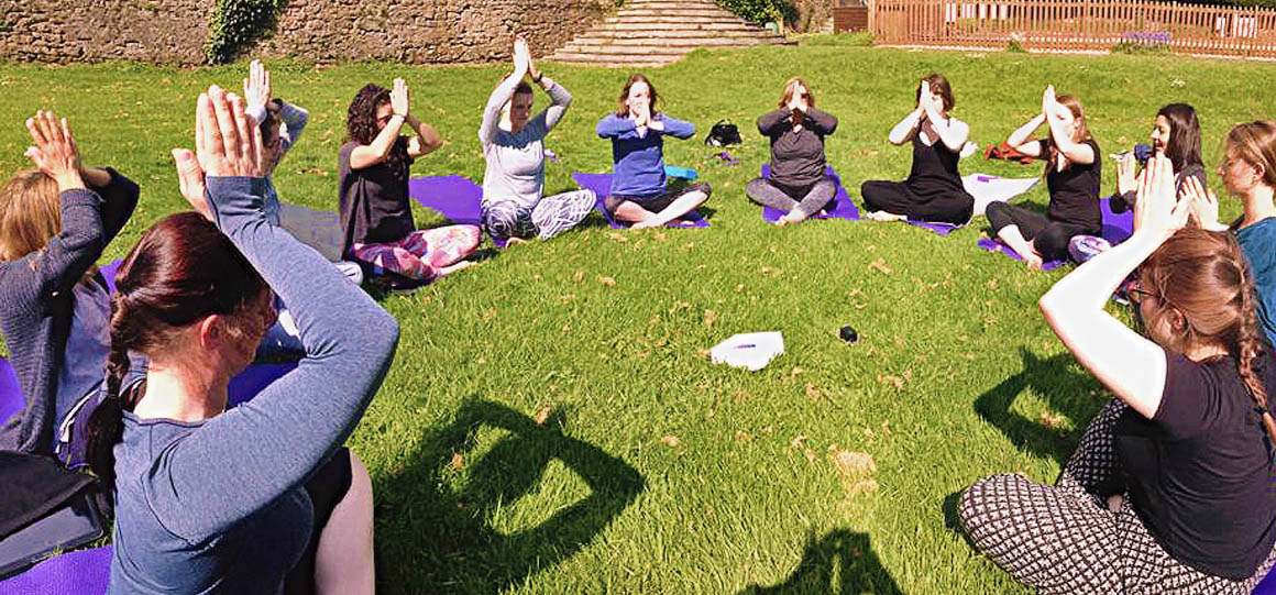 Group of young women meditating together in a circle
