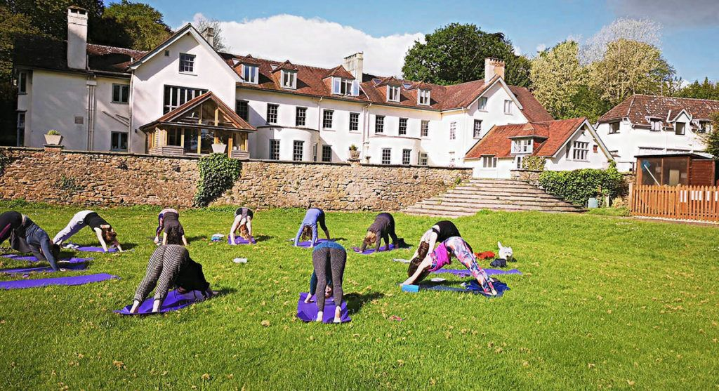 Group of young women practising yoga together in a cirlce